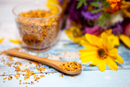 bee on flower: Focused spoon with pollen on the table, glass with pollen and colorful flower in the background Stock Photo