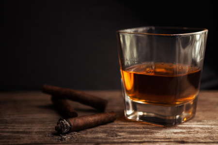 Cigar and glass with brandy on wooden table