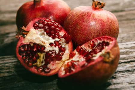 Sliced pomegranate and raw pomegranate on wooden background Stock Photo