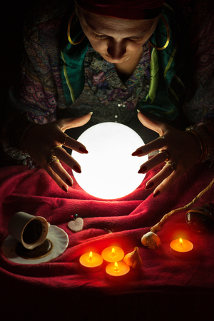 Female fortuneteller with her hands above lighted crystal ball Stock fotó