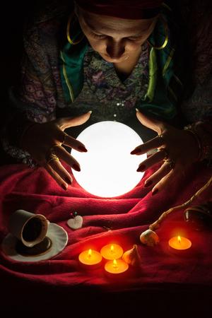 Vrouwelijke fortuneteller met haar handen boven de verlichte kristallen bol Stockfoto