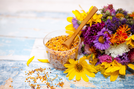 bee on flower: Bee pollen in plastic glass with wooden spoon on the table
