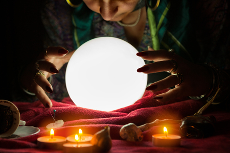 esoterism: Fortune teller woman looking at shining crystal ball