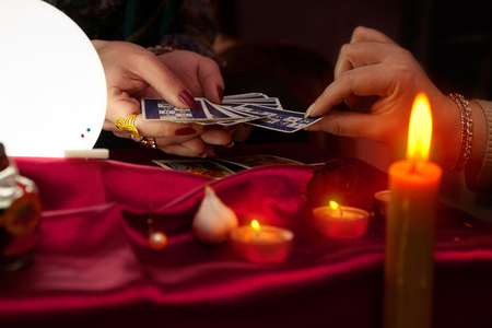 Fortune teller woman giving tarot card to another woman for future telling 스톡 콘텐츠