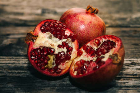 Two half of pomegranate and one whole raw pomegranate