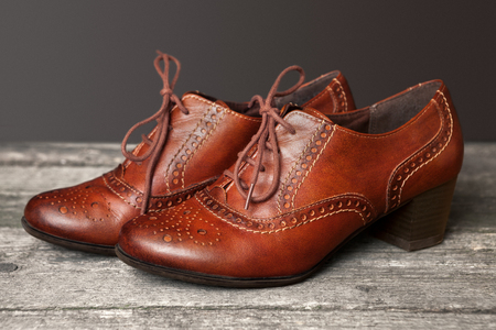 reflective: Elegant brown shoes on old wooden table