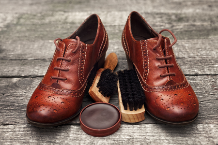Pair of elegant shoes with brush and polish cream