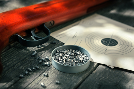 Pellets,air rifle and target on wooden table