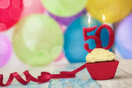 Candela in cima a cupcake compleanno, celebrazione del cinquantesimo compleanno Archivio Fotografico - 87525803