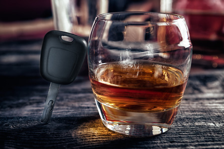 Glass of whiskey and car keys on wooden bar table Stock Photo