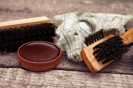 Brush, dirty cloth and polish cream, shoe cleaning accessories Archivio Fotografico