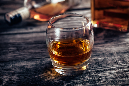 Glass with alcohol drink whiskey on bar table