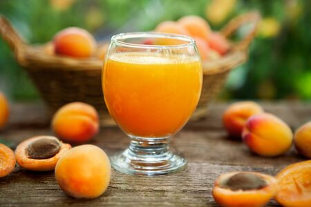 Fresh apricot juice in glass with fresh apricots on the table