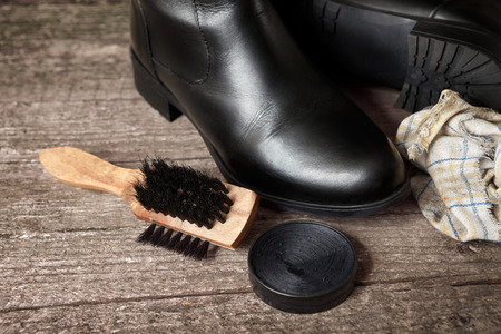 Polish cream, cloth and wooden brush with black shoes