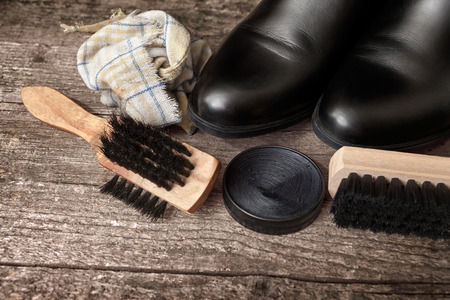 Wooden brushes and polish cream for shoes and boots on wooden table Stock Photo