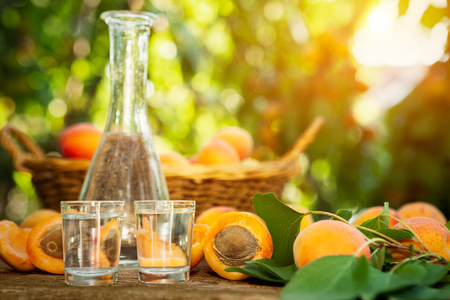 Fruit brandy in a glass and apricots on wooden table