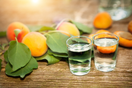 Shot glass with apricot brandy and apricot with leaf on the table