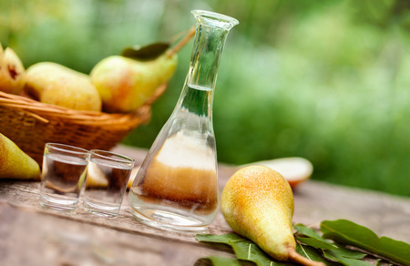 Pears and bottle with pear brandy on the table Stock Photo