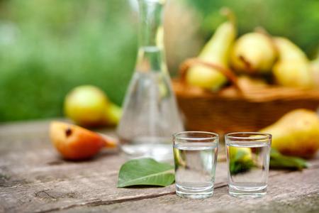 木のテーブルの上のショットガラスの梨アルコール飲料