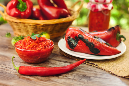 Ajvar in bowl with red paprika on the table