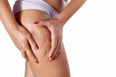 Woman squeezing her thigh with hands to show cellulite