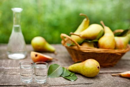 Pear brandy in shot glass.Fresh pears in background.