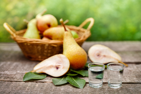 Ripe pears and pear fruit brandy alcohol drink in shot glass Standard-Bild