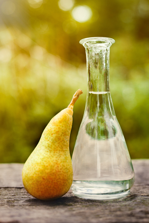 desk: Fresh pear and fruit brandy in bottle on wooden table