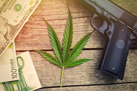 Leaf of marihuana with gun and banknotes on wooden background