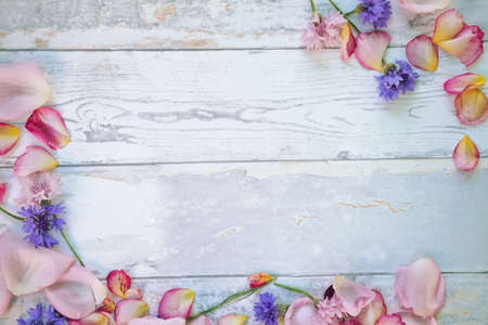 Decorative petals and fallen flowers on wooden table
