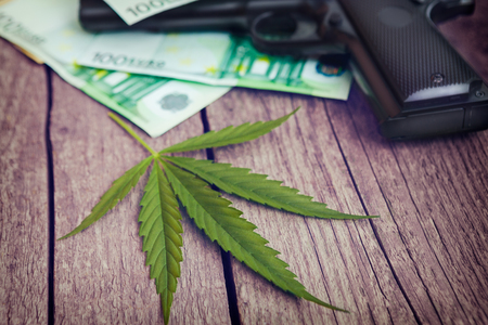 Marijuana leaf with gun and money bills on wooden table