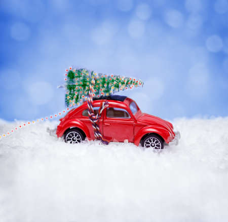 Christmas concept with car toy carrying a Christmas tree on background with snowflakes