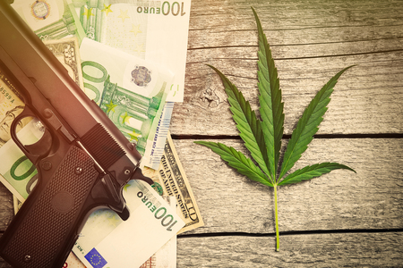 Marihuana with pistol and money bills on wooden table Standard-Bild