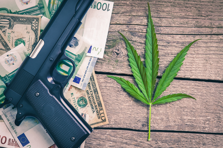 Marihuana leaf with banknotes and weapon on the table
