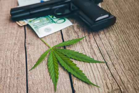 Cannabis leaf with gun and money bills on wooden table