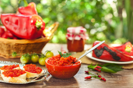 Delicious ajvar in bowl with spoon on the table
