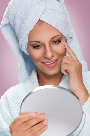 Young woman holding mirror and applying cream on her face