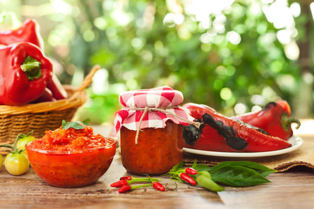 Ajvar in a jar and glass bowl on the table Standard-Bild