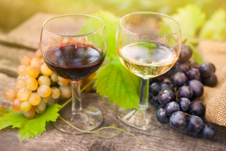 Red and white wine glasses with grapes on wooden surface Standard-Bild