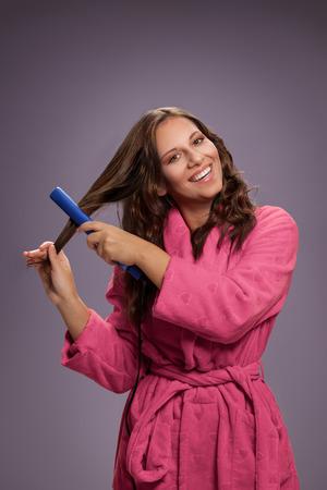Junge Frau mit dem Haarstrecker, der Haar anredet