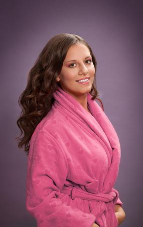 Porträt der recht jungen Frau mit dem gesunden Haar, das im rosa Bademantel aufwirft Standard-Bild