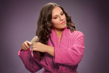 Young woman brushing hair with comb