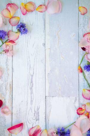 Hölzerner Hintergrund mit gefallenen Blumenblättern und Blumen um es
