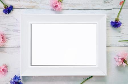 Weißes Rahmenmodell mit gefallenen Blumen im Hintergrund
