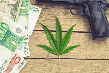 Marihuana leaf on wooden background with gun and money bills Standard-Bild