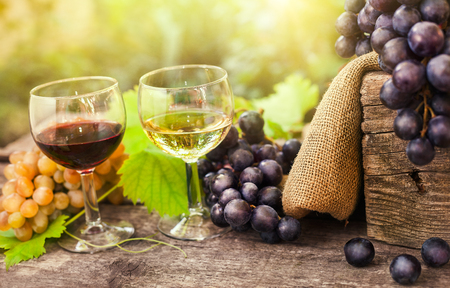 Glass of red and white wine with grapes on old wooden table