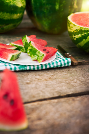 Plate with watermelon pieces with watermelons in the background