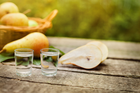 Pear brandy in shot glass and pears on the table