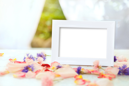 White picture frame on wooden table with petals and flowers Standard-Bild