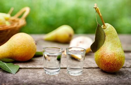 Pear with leaf and shot glass with fruit brandy on the table Standard-Bild